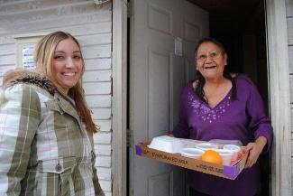 Woman receiving her Meals on Wheels delivery