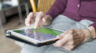 Older person holding a tablet device