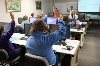 People in a classroom learning computer skills